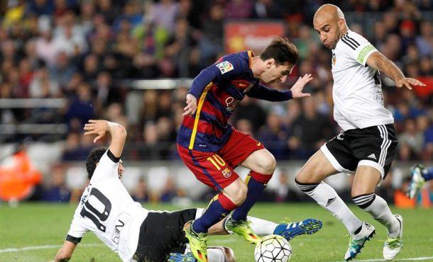 El delantero argentino del FC Barcelona Leo Messi (c) lucha con Dani Parejo (i) y el defensa tunecino Abdennour (d), del Valencia CF, durante el partido de la trigésimo tercera jornada de Liga en Primera División que se jugó en el Campo Nuevo, en Barcelona. Efe.