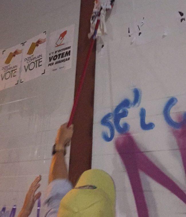 Jóvenes catalanes arrancan carteles ilegales del 1-O en las calles de Cataluña
