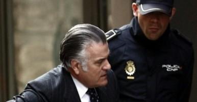 Luis Bárcenas, el extesorero del PP, accediendo a los juzgados custodiado por un agente de Policía / EFE