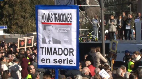 """""""Rajoy timador en serie"""", con este letrero manifestantes de AVT han acusado a Rajoy de seguir las políticas de Zapatero"""