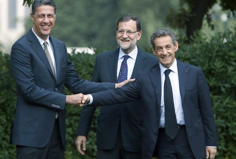 El candidato del PPC al 27-, Xavier García Albiol (i), saluda al expresidente francés, Nicolas Sarkozy (d), en presencia del presidente del Gobierno, Mariano Rajoy (c), momentos antes de mantener un encuentro previo al mitin de cierre de campaña de los populares para las elecciones del 27S. Efe