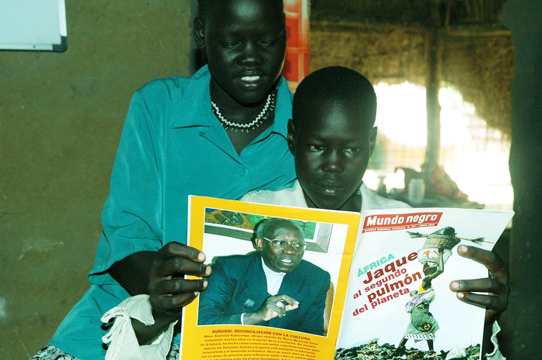 Dos joven africano subsahariano leyendo una noticia en lengua española del periodíco africano 'Mundo Negro' en una imagen de este medio. Lasvocesdelpueblo.