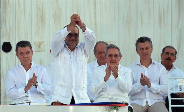 """El máximo líder de las Fuerzas Armadas Revolucionarias de Colombia (FARC), Rodrigo Londoño Echeverri (frente), alias alias """"Timochenko"""", saluda tras firmar el acuerdo de paz frente al presidente de Colombia, Juan Manuel Santos (i), y los presidentes de Cuba, Raúl Castro (3-d), y de Argentina, Mauricio Macri (2-d), en la ceremonia de la firma del acuerdo de paz en la ciudad de Cartagena. EFE"""
