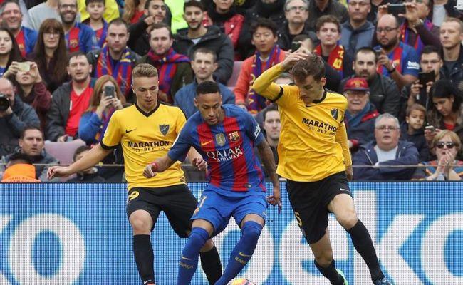 El delantero brasileño del FC Barcelona Neymar jr (c) intenta avanzar con el balón ante el centrocampista Javier Ontiveros (i) y el defensa Diego Llorente (d), del Málaga CF, durante el partido de la duodécima jornada de Liga de Primera División que se jugó en el Campo Nuevo. Efe