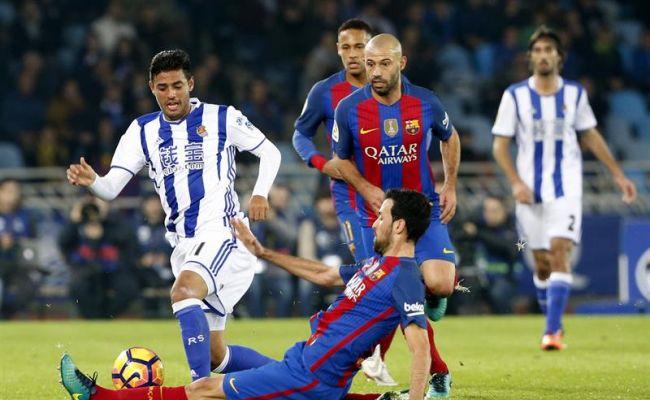 El delantero mexicano de la Real Sociedad, Carlos Vela (i), intenta llevarse el balón ante la entrada del centrocampista del F. C. Barcelona, Sergio Busquets, durante el encuentro correspondiente a la jornada 13 de primera división, en el estadio Anoeta de San Sebastián. Efe.