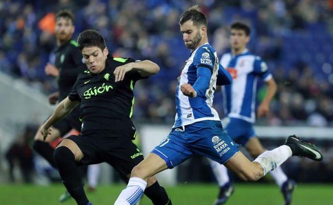 El delantero brasileño del RCD Español Leo Baptistao (d) intenta rematar junto al defensa Jorge Meré (i), del Real Sporting de Gijón, durante el partido de la decimoquinta jornada de Liga jugado en el RCDE Stadium de Barcelona. Efe