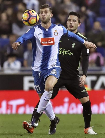 El delantero brasileño del RCD Espanyol Leo Baptistao (i) intenta rematar ante la presencia del centrocampista Isma López B. (d), del Real Sporting de Gijón, durante el partido de la decimoquinta jornada de Liga jugado en el RCDE Stadium de Barcelona. Efe