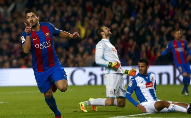 El delantero uruguayo del FC Barcelona 'el caníbal' Luis Suárez (i) celebra el primer gol marcado frente al RCD Español, durante el partido de la decimosexta jornada de primera división en el estadio del Campo Nuevo, en Barcelona. Efe.