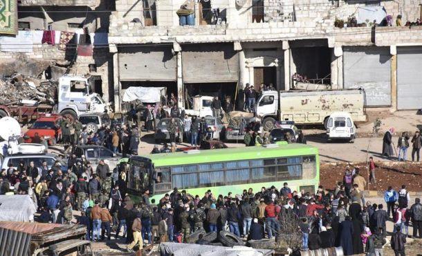 Fotografía facilitada por la Agencia Árabe Siria de Noticias (SANA), que muestra a los civiles, combatientes y sus familiares accediendo a uno de los autobuses durante los trabajos de evacuación de los barrios rebeldes de Alepo, Siria, el jueves. Efe.