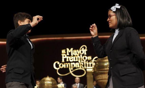 Los niños de San Ildefonso Youssef y Nicol muestran el tercero de los quintos premios, dotado con 60.000 euros la serie y con 6.000 euros cada décimo, que ha recaido en el número 39.415 en el Sorteo Extraordinario de la Lotería de Navidad que se celebra esta mañana en el Teatro Real de Madrid. EFE