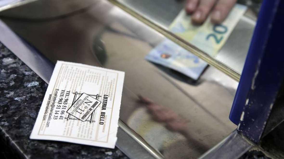 Una persona compra un décimo de Lotería de Navidad en una administración de Valencia Archivo Efe
