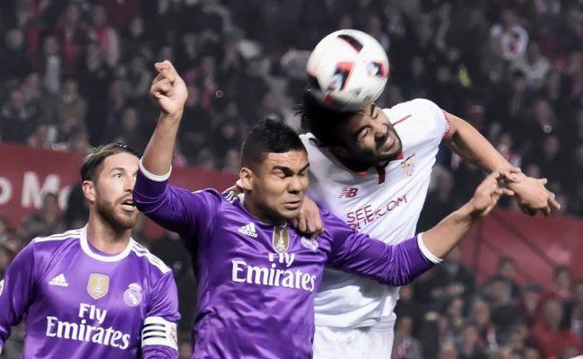 El centrocampista del Sevilla CF Vicente Iborra (d) salta por el balón con el brasileño Casemiro, del Real Madrid, durante el partido de vuelta de octavos de final de la Copa del Rey que se juega esta noche en el el estadio Ramón Sánchez-Pizjuán, en Sevilla. Efe.