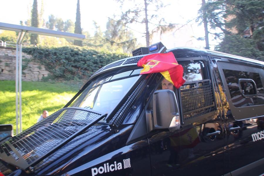 Un furgón de los Mozos lleva muy a su pesar a una bandera de España en Manresa (Barcelona)