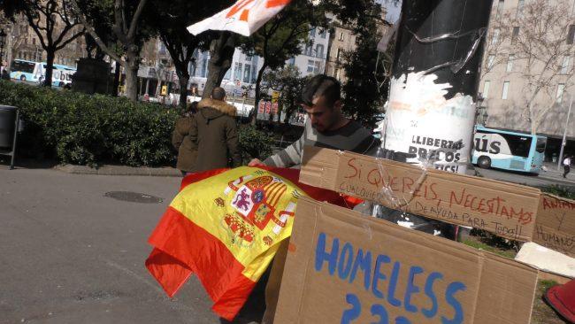 Un sintecho ondea su bandera de España ante sus compañeros separatistas