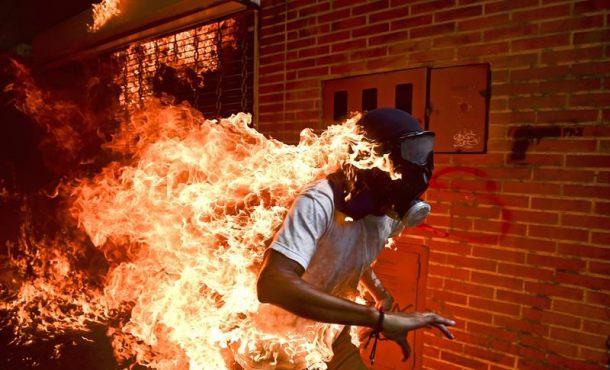 Un pacífico corre envuelto en llamas alcanzado por un chorro de gasolina del chavismo